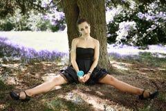 Muchacha hermosa joven del retrato que se sienta sobre árbol con el caramelo de la piruleta Imagen de archivo