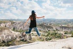 Muchacha hermosa joven del viaje encima de una colina en Cappadocia, Turquía Ella salta para arriba Viaje, éxito, libertad, logro imagen de archivo libre de regalías