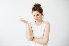 Muchacha hermosa joven descontentada con el bollo que gesticula sobre el fondo blanco Foto de archivo