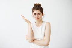 Muchacha hermosa joven descontentada con el bollo que gesticula sobre el fondo blanco Fotos de archivo libres de regalías