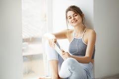 Muchacha hermosa joven en auriculares que sonríe mirando la tableta de la tenencia de la cámara que escucha fluir la música que s Foto de archivo libre de regalías