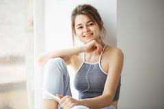 Muchacha hermosa joven en auriculares que sonríe mirando la tableta de la tenencia de la cámara que escucha fluir la música que s Foto de archivo