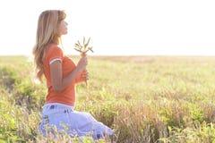 Muchacha hermosa joven en el campo con los oídos en la mano Imágenes de archivo libres de regalías