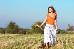 Muchacha hermosa joven en el campo con los oídos en la mano Imagen de archivo libre de regalías