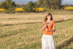 Muchacha hermosa joven en el campo con los oídos en la mano Fotografía de archivo