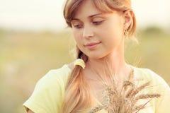 Muchacha hermosa joven en el campo con los oídos en la mano Foto de archivo libre de regalías