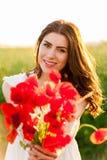 Muchacha hermosa joven en el campo con un ramo de las amapolas Foto de archivo