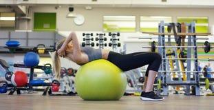Muchacha hermosa joven en el gimnasio, oscilaciones la prensa con la bola para la aptitud, mejorando los músculos de la prensa y  Imagen de archivo libre de regalías