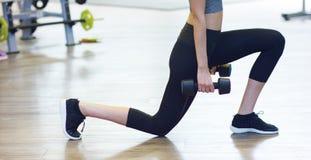 Muchacha hermosa joven en el gimnasio que hace ejercicios en la posición en cuclillas con un barbell, mejorando los músculos de l Imágenes de archivo libres de regalías