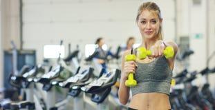 Muchacha hermosa joven en el gimnasio que hace ejercicios en la posición en cuclillas con un barbell, mejorando los músculos de l Foto de archivo libre de regalías