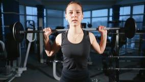 Muchacha hermosa joven en el gimnasio que hace ejercicios en la posición en cuclillas con un barbell, mejorando los músculos de l almacen de video
