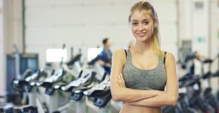 Muchacha hermosa joven en el gimnasio, soportes sonriendo con una toalla en su hombro después de entrenar y relajada Concepto: al Foto de archivo