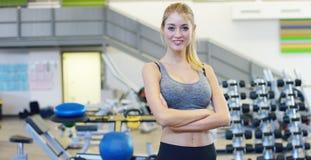 Muchacha hermosa joven en el gimnasio, soportes sonriendo con una toalla en su hombro después de entrenar y relajada Concepto: al Imágenes de archivo libres de regalías