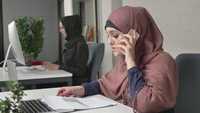 Muchacha hermosa joven en el hijab rosado que trabaja con los documentos y que habla en el teléfono móvil Mujeres árabes en la of almacen de video