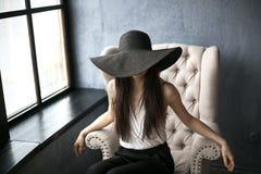 Muchacha hermosa joven en el sombrero negro grande La muchacha se sienta elegante en una silla blanca Imagen de archivo