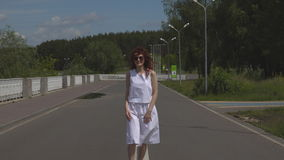 Muchacha hermosa joven en gafas de sol y un vestido blanco que caminan al aire libre almacen de metraje de vídeo