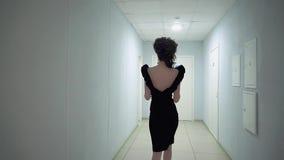 Muchacha hermosa joven en la oficina, en el vestido de noche, caminando a lo largo del pasillo Cámara lenta almacen de metraje de vídeo