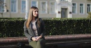 Muchacha hermosa joven en la ropa casual que se sienta en un banco en un parque metrajes