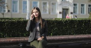 Muchacha hermosa joven en la ropa casual que se sienta en un banco y que habla en el teléfono móvil almacen de video