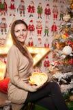 Muchacha hermosa joven en las decoraciones del Año Nuevo en el fondo del papel pintado con la gente colorida Imagenes de archivo