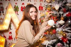 Muchacha hermosa joven en las decoraciones del Año Nuevo en el fondo del papel pintado con la gente colorida Imagen de archivo libre de regalías