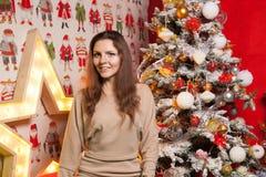 Muchacha hermosa joven en las decoraciones del Año Nuevo en el fondo del papel pintado con la gente colorida Foto de archivo libre de regalías