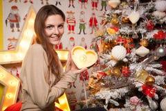 Muchacha hermosa joven en las decoraciones del Año Nuevo en el fondo del papel pintado con la gente colorida Foto de archivo