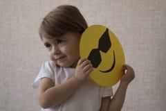 Muchacha hermosa joven en las sonrisas y los controles blancos de la camisa en sus manos un papel amarillo con una cara feliz del Imagen de archivo libre de regalías
