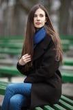 Muchacha hermosa joven en los vidrios azules de una bufanda de la capa negra que se sientan en banco en parque de la ciudad Una m Fotografía de archivo