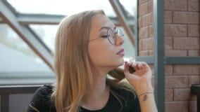 Muchacha hermosa joven en los vidrios que se sientan en un café por la ventana que mira los lados metrajes