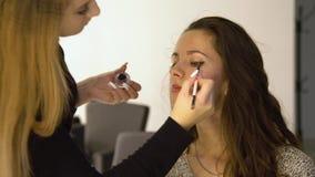 Muchacha hermosa joven en salón de belleza El artista de maquillaje construye 4K almacen de metraje de vídeo