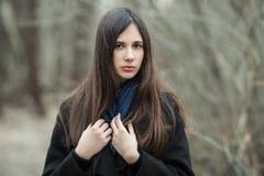 Muchacha hermosa joven en un cierre azul de la bufanda de la capa negra para arriba en el otoño/la primavera Forest Park Una much Fotografía de archivo
