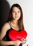 Muchacha hermosa joven en un corsé de cuero con el cordón y la falda, almohada roja del corazón de la tenencia Imagen de archivo