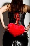 Muchacha hermosa joven en un corsé de cuero con el cordón y la falda, almohada roja del corazón de la tenencia Fotografía de archivo libre de regalías