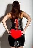 Muchacha hermosa joven en un corsé de cuero con el cordón y la falda, almohada roja del corazón de la tenencia Fotos de archivo