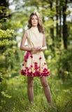 Muchacha hermosa joven en un vestido amarillo en el bosque Retrato de la mujer romántica en adolescente de moda imponente del bos Fotos de archivo libres de regalías