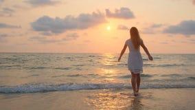 Muchacha hermosa joven en un vestido blanco que camina a lo largo de la playa Oc?ano almacen de metraje de vídeo