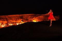 Muchacha hermosa joven en un vestido corto rojo cerca del cráter ardiente en la noche el retocar del arte foto de archivo libre de regalías