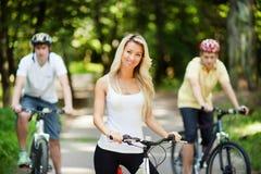 Muchacha hermosa joven en una bicicleta con dos hombres en el fondo Imágenes de archivo libres de regalías