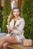 Muchacha hermosa joven en una capa beige, llamando por el teléfono, sentándose Imagen de archivo libre de regalías