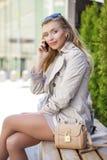 Muchacha hermosa joven en una capa beige, llamando por el teléfono, sentándose Imagen de archivo