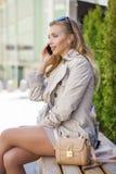 Muchacha hermosa joven en una capa beige, llamando por el teléfono, sentándose Fotografía de archivo