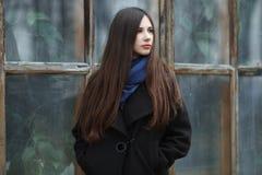 Muchacha hermosa joven en una capa negra y una bufanda azul para una presentación en el parque del otoño/de la primavera Una much Imagen de archivo libre de regalías