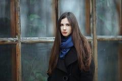 Muchacha hermosa joven en una capa negra y una bufanda azul para una presentación en el parque del otoño/de la primavera Una much Imagen de archivo