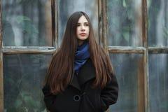 Muchacha hermosa joven en una capa negra y una bufanda azul para una presentación en el parque del otoño/de la primavera Una much Fotos de archivo libres de regalías