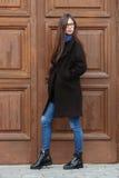 Muchacha hermosa joven en una capa negra y una bufanda azul que se divierten Muchacha morena elegante con el pelo extralargo magn Imagen de archivo