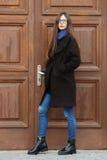 Muchacha hermosa joven en una capa negra y una bufanda azul que se divierten Muchacha morena elegante con el pelo extralargo magn Fotos de archivo