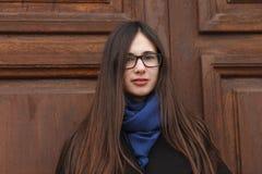 Muchacha hermosa joven en una capa negra y una bufanda azul que se divierten Muchacha morena elegante con el pelo extralargo magn Fotografía de archivo