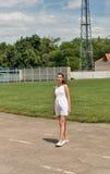 Muchacha hermosa joven en vestido blanco corto con el pelo azotado por el viento Foto de archivo libre de regalías