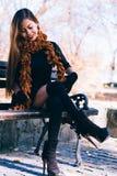 Muchacha hermosa joven en vestido negro con la bufanda marrón que se sienta en el banco Imagenes de archivo